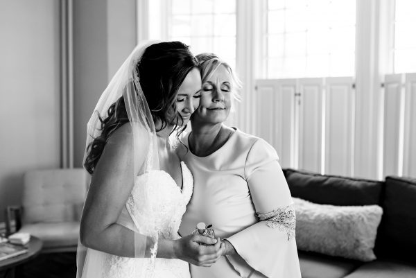 Mother and daughter embrace while bride gets ready for her wedding. Photo taken by April & Bryan Photography in Lancaster, PA