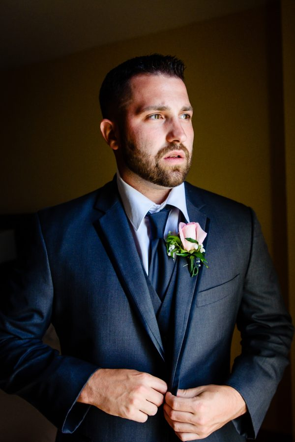 Groom wearing a navy blue suit and pink rose boutonnière. Photo taken by April & Bryan Photography in Lancaster, PA