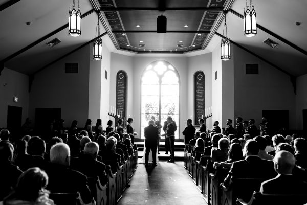 Black and white image of a couple getting married in a church, surrounded by their family and friends. Photo taken by April & Bryan Photography in Lancaster, PA