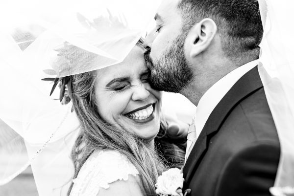 Groom kisses bride on the forehead while she laughs under her bridal veil. Photo taken by April & Bryan Photography in Lancaster, PA