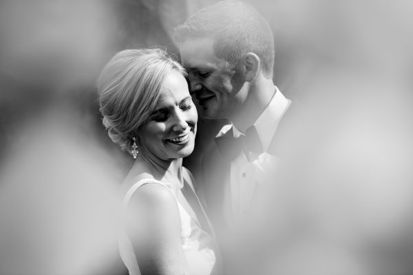 Black and white image of a bride and groom laughing and embracing on their wedding day. Photo taken by April & Bryan Photography in Lancaster, PA