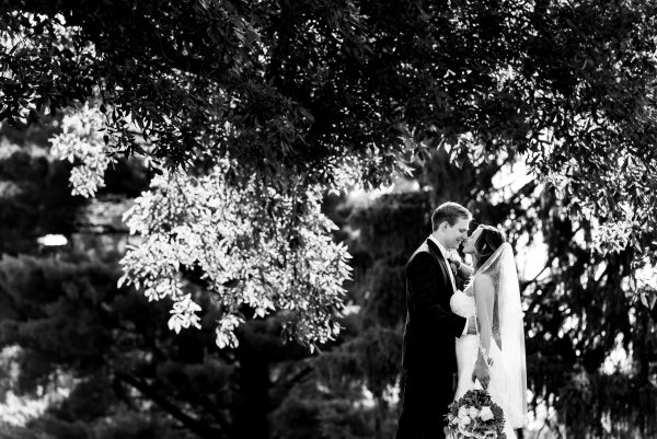 Black and white image of a bride and groom kissing, surrounded by trees. Photo taken by April & Bryan Photography in Lancaster, PA