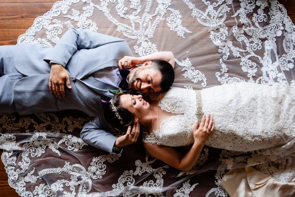 Bride and groom embrace on the floor with their faces touching. Photo taken by April & Bryan Photography in Lancaster, PA