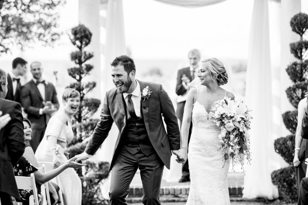Black and white image of a happy bride and groom as they walk back down the aisle at White Chimneys in Lancaster, PA. Photo by April & Bryan Photography.