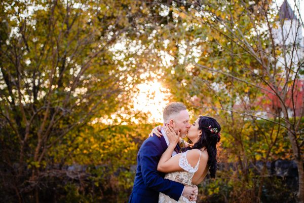 Bride and groom kissing against a backdrop of trees and a sunset. Photo taken by April & Bryan Photography in Lancaster, PA