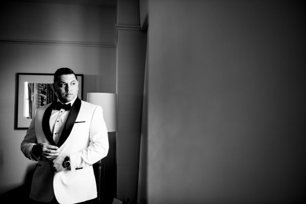 A groom getting ready in a black and white picture. Photo taken by April & Bryan Photography in Lancaster, PA.