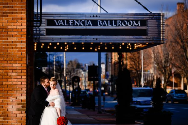 Bride and groom embrace against a brick wall outside of the Valencia Ballroom. Photo taken by April & Bryan Photography in Lancaster, PA