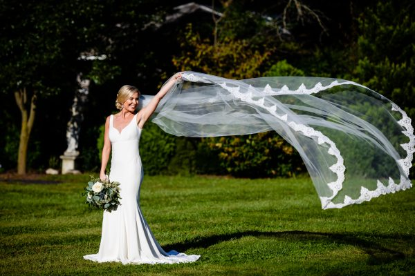 Bride playing with her large veil as it floats in the air. Photo taken by April & Bryan Photography in Lancaster, PA.