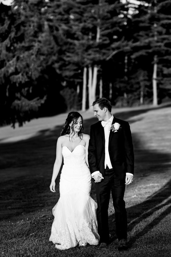 Black and white image of a couple on their wedding day walking side-by-side while holding hands. Photo taken by April & Bryan Photography in Lancaster, PA