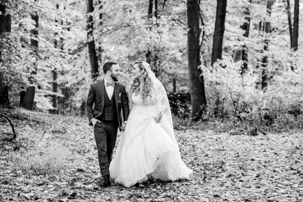 Black and white image of a couple walking hand and hand through the woods on their wedding day. Photo taken by April & Bryan Photography in Lancaster, PA