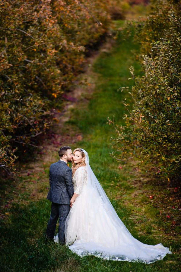 Groom kissing his bride on the cheek on their wedding day. The bride is wearing a long, white, and flowing wedding dress as they stand in an orchard. Photo taken by April & Bryan Photography in Lancaster, PA
