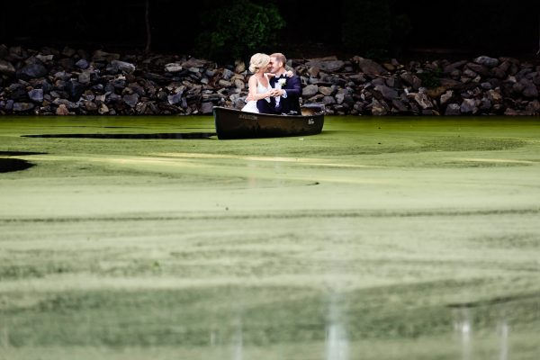 A kissing newlywed couple in a boat on an algae green pond. Photo taken by April & Bryan Photography in Lancaster, PA
