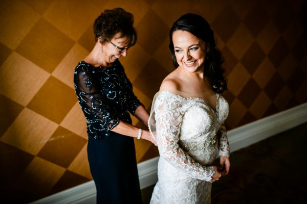 A bride getting buttoned into her wedding dress by her mother on her wedding day. Photo taken by April & Bryan Photography in Lancaster, PA