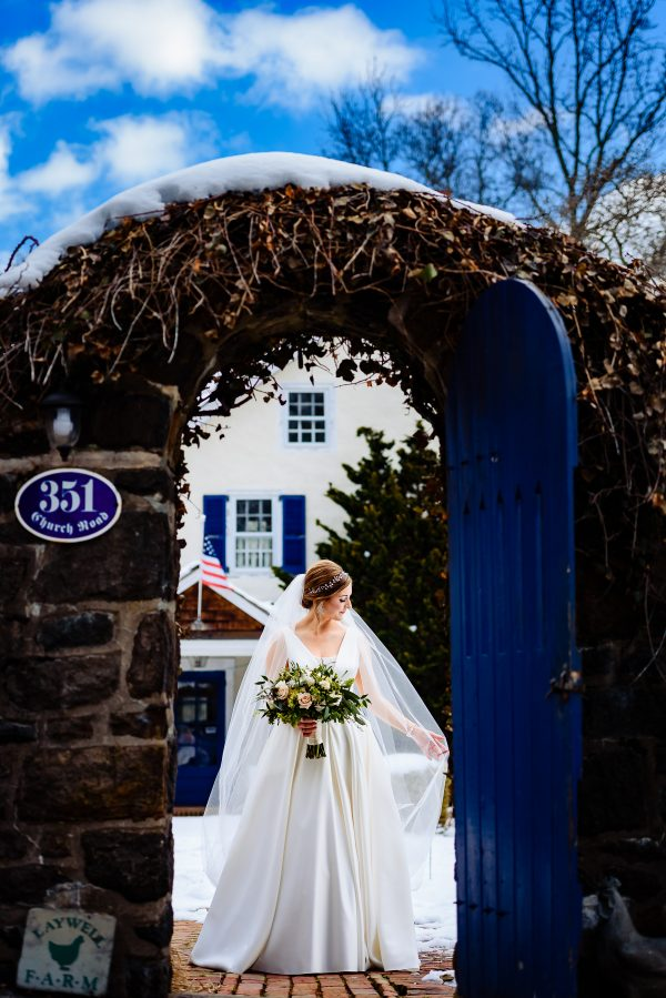 Bride with a long veil and wedding bouquet standing under an arch with an open blue door. Photo taken by April & Bryan Photography in Lancaster, PA.