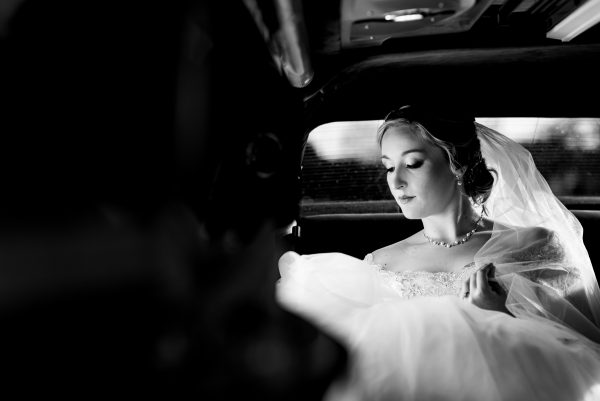 Black and white picture of a bride wearing her wedding dress and sitting in a car on the way to her wedding. Photo taken by April & Bryan Photography in Lancaster, PA