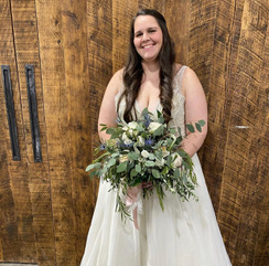 Smiling woman holding a bouquet and wearing a white wedding dress