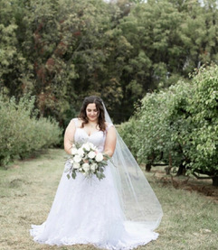Woman staring down at her bouquet wearing a white wedding dress and long veil