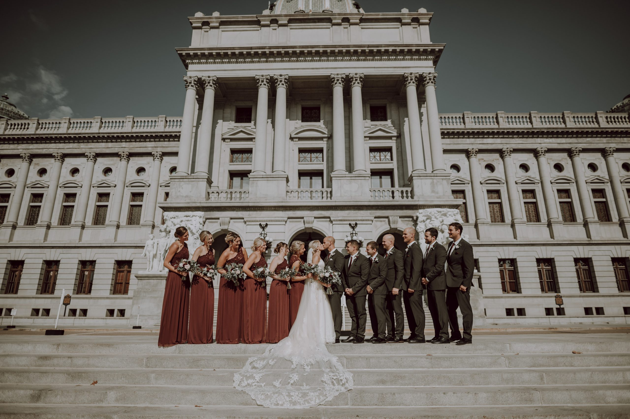 The whole bridal party watching a lifetime of love in the making. Captured by Lovefusion Photography at Stock's Manor in Mechanicsburg, PA. Featured on Dream Weddings.