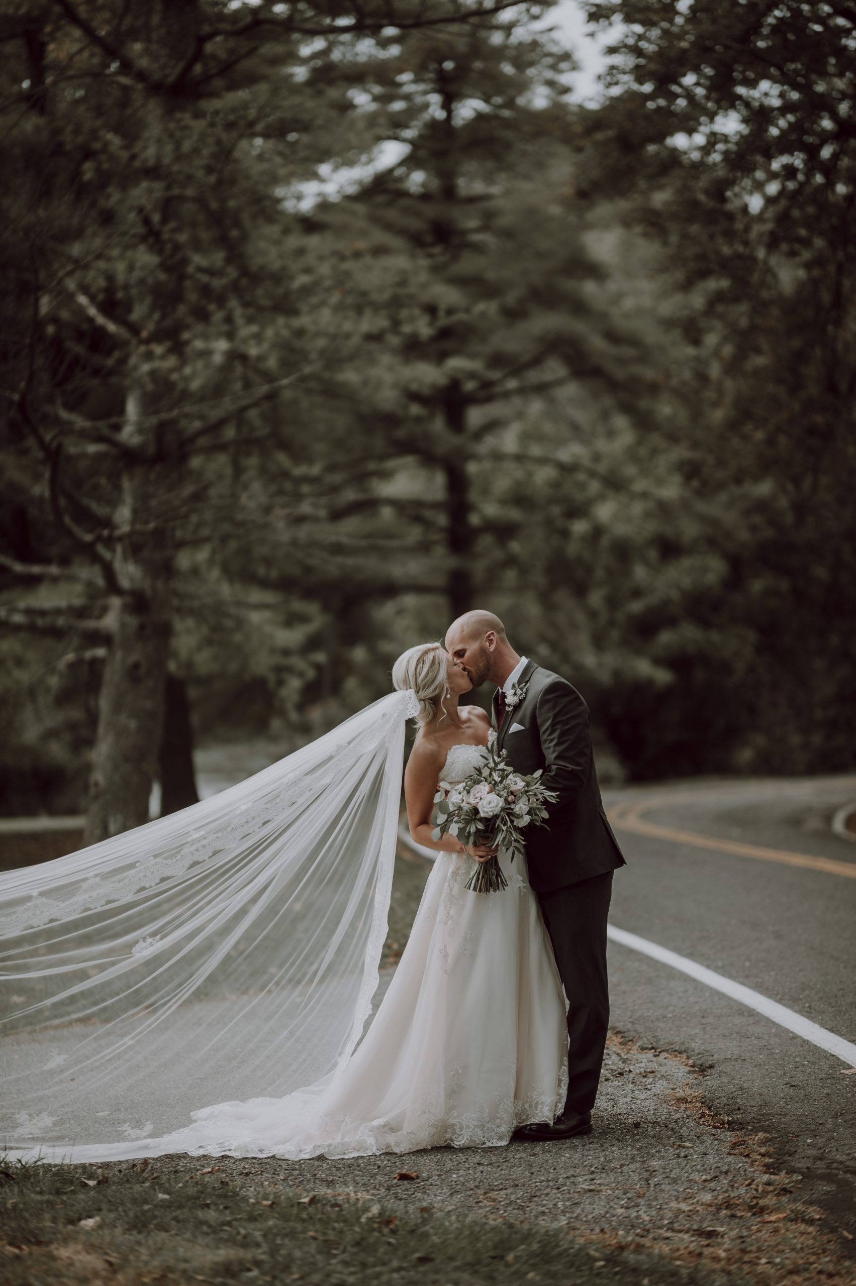 A veil that so beautifully frames the blushing bride. Captured by Lovefusion Photography at Stock's Manor in Mechanicsburg, PA. Featured on Dream Weddings.