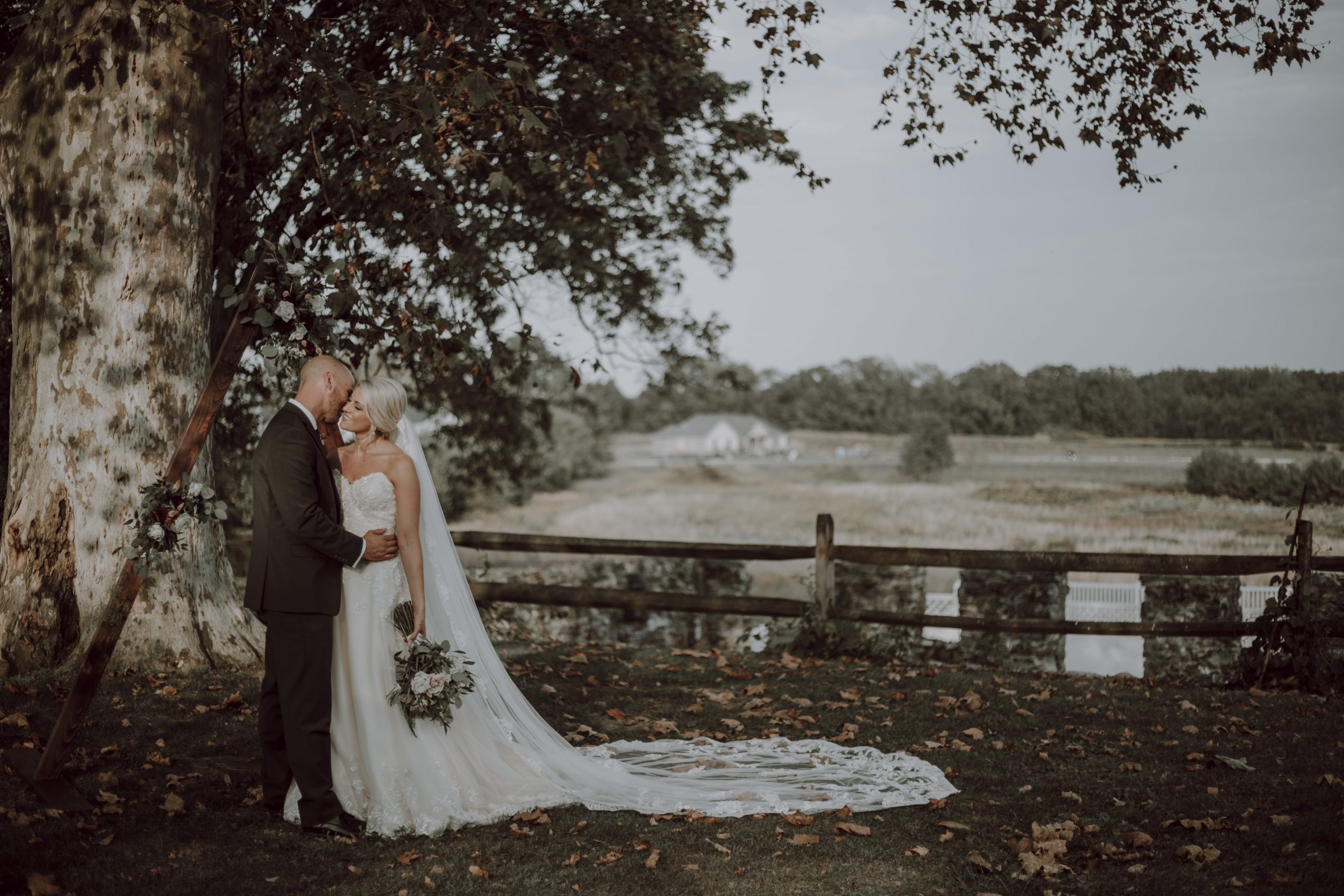 Sharing a moment under the shade of a large tree in the pasture. Captured by Lovefusion Photography at Stock's Manor in Mechanicsburg, PA. Featured on Dream Weddings.