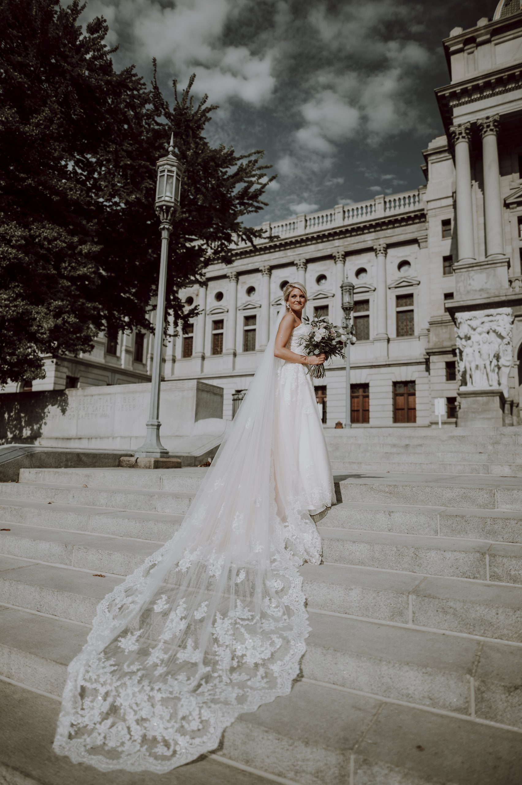 A wonderfully romantic veil cascades down the steps of the capital. Captured by Lovefusion Photography at Stock's Manor in Mechanicsburg, PA. Featured on Dream Weddings.