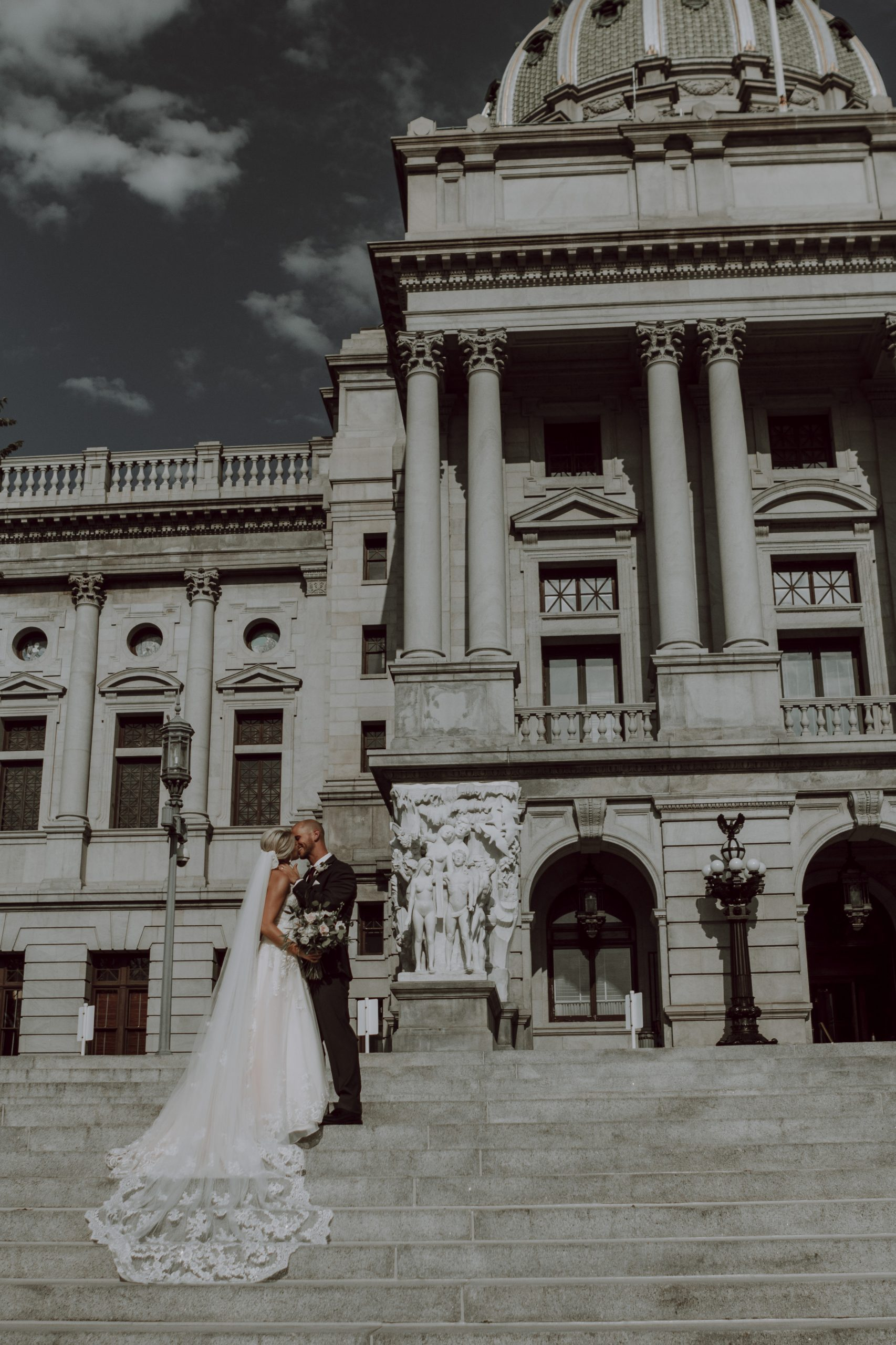 A smiling kiss. Captured by Lovefusion Photography at Stock's Manor in Mechanicsburg, PA. Featured on Dream Weddings.