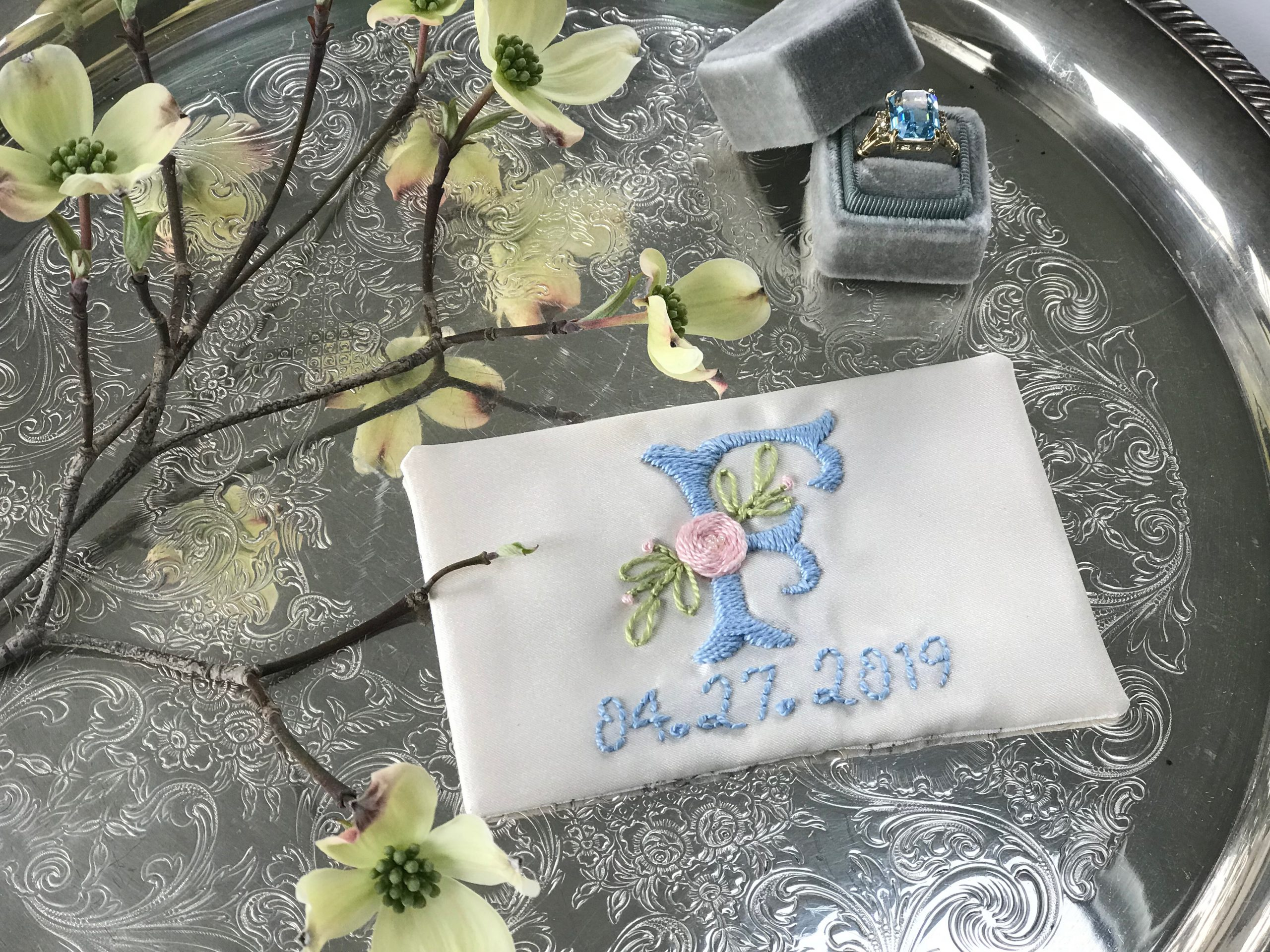 An 'F' embroidered on the ring bearer's pillow for a Spring wedding on April 4, 2019. Work by Megan Hamilton Weddings. Featured on Dream Weddings.