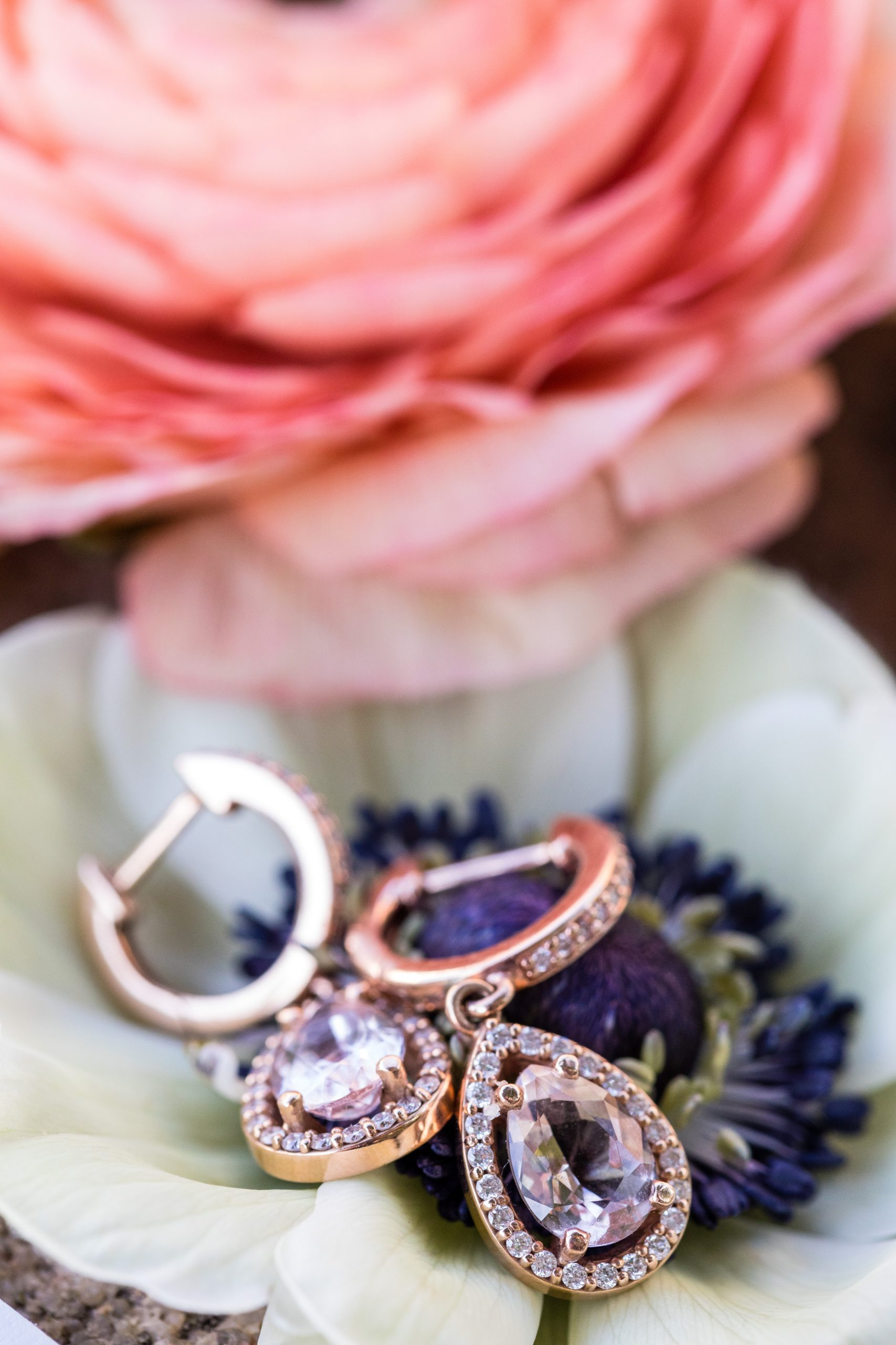 Dangling rose gold earrings lay in the center of a flower outlined in diamonds at the Michener Museum styled urban contemporary shoot for Ashley Gerrity Photography this past Summer. Featured on Dream Weddings.