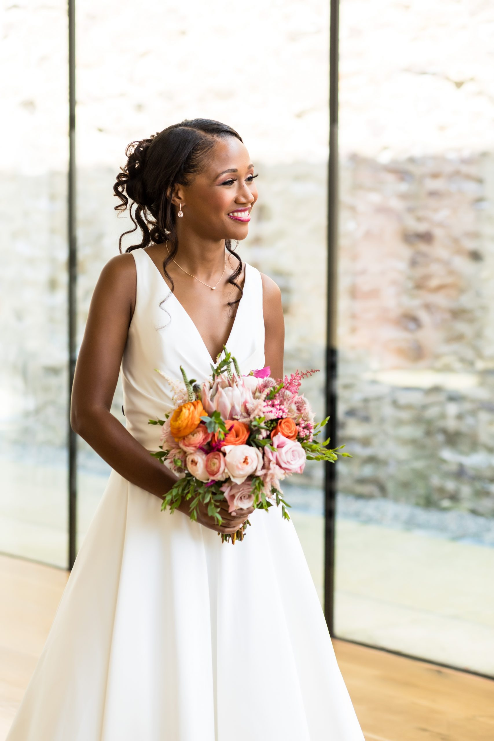 The bride happily looks on through the floor to ceiling windows at the Michener Museum styled urban contemporary shoot for Ashley Gerrity Photography this past Summer. Featured on Dream Weddings.