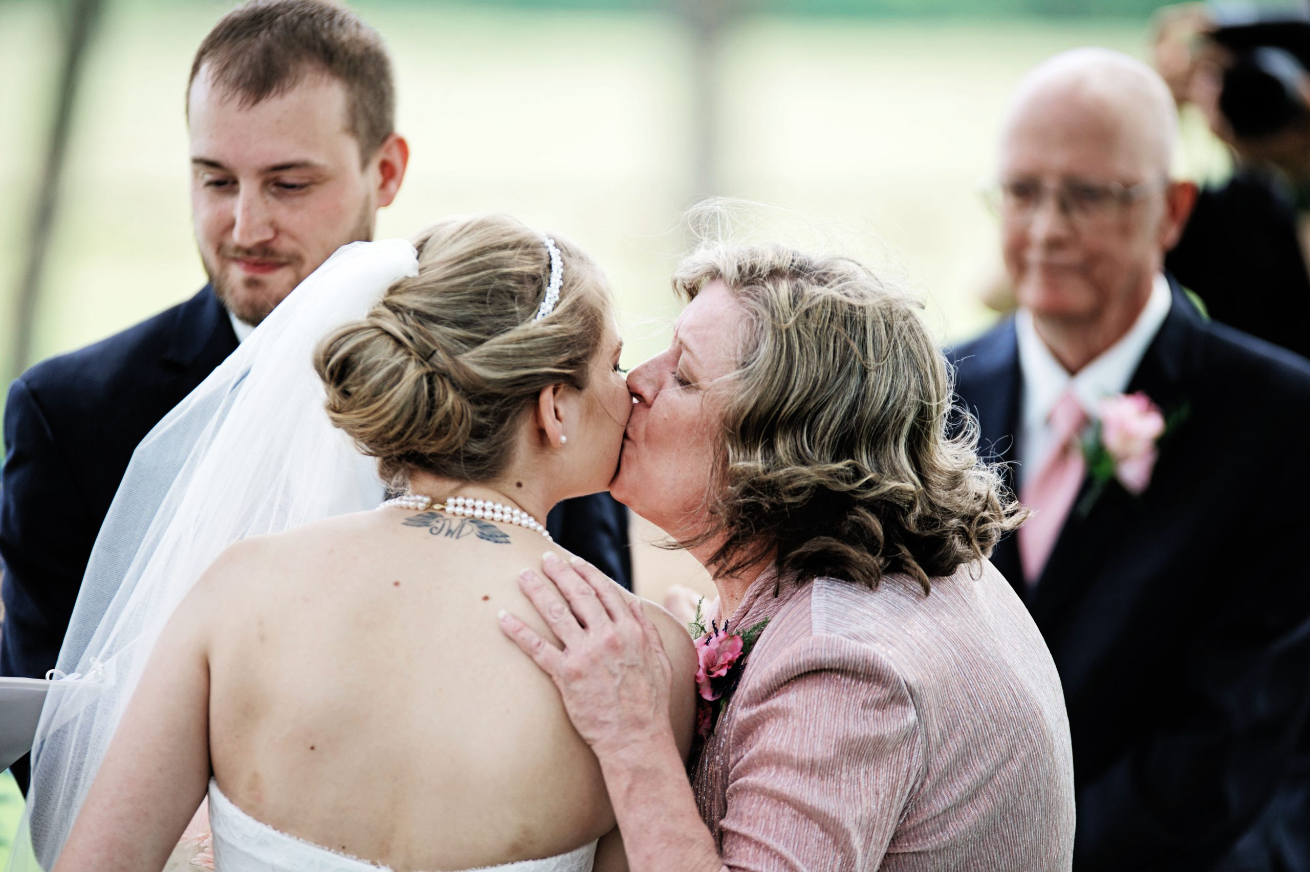 Mother and daughter exchange kisses before starting the wedding ceremony located at Lakeview Farms of York, PA. Lovefusion had the privilege to photograph these special moments. Featured in Dream Weddings.