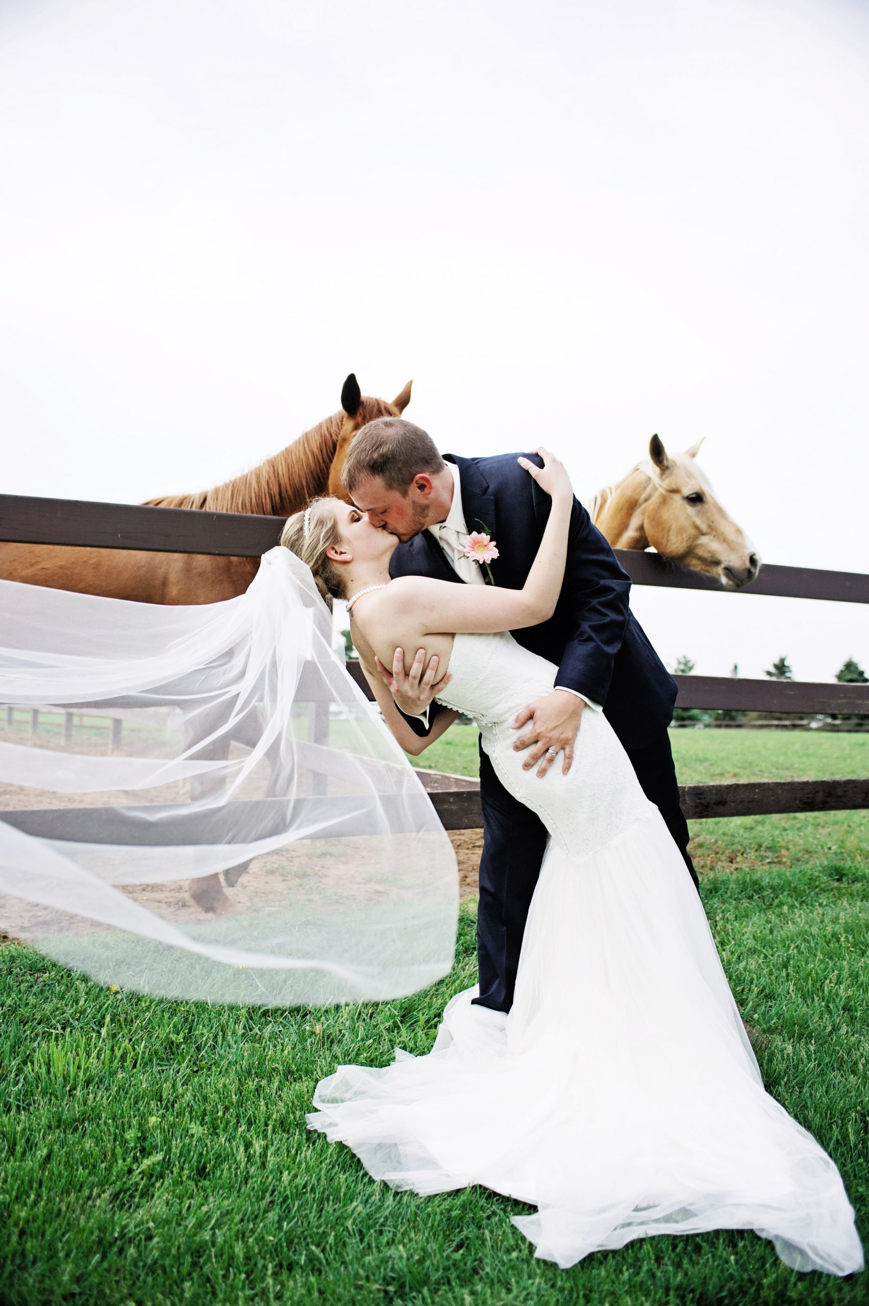Veil flowing in the breeze, Lovefusion Photography captures a warm embrace of bride and groom at Lakeview Farms, in York, PA. Featured on Dream Weddings.