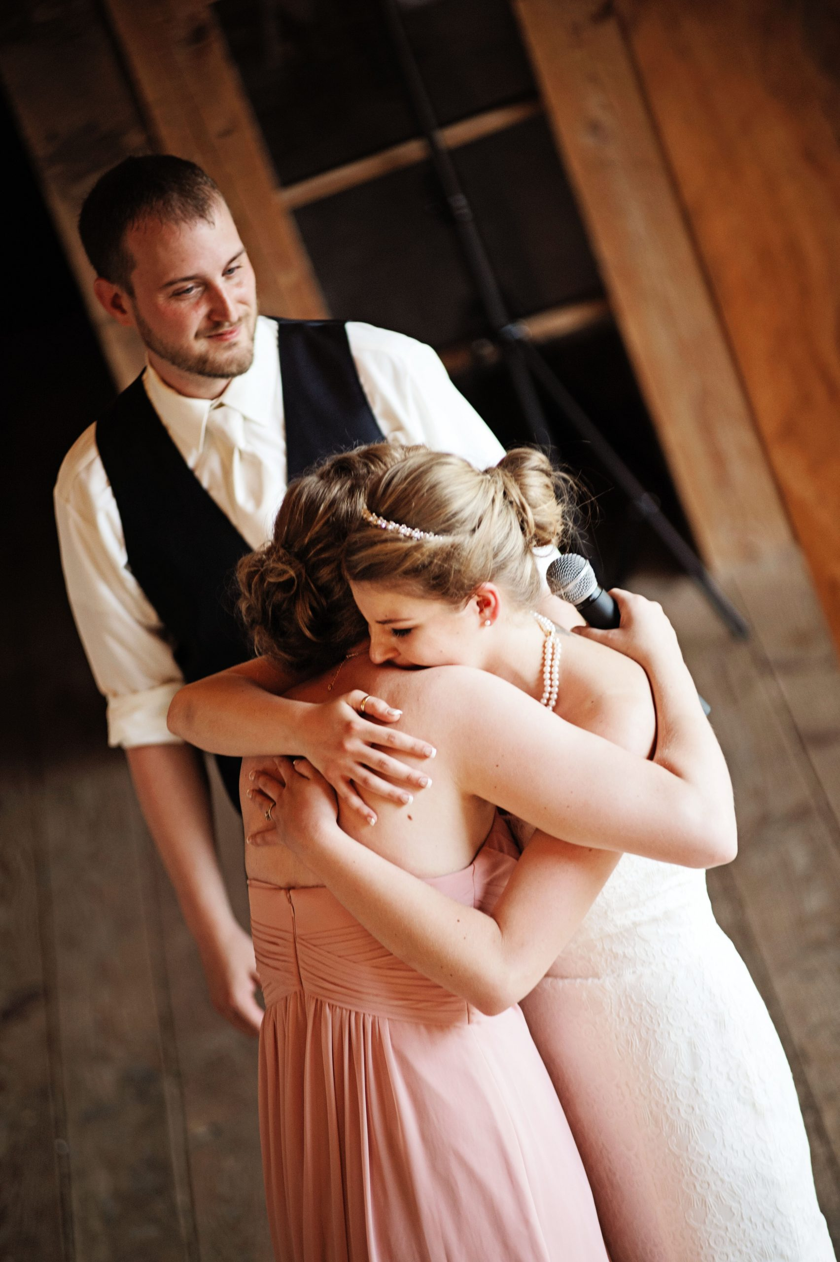 The bride shares a hug with the maid of honor as she finishes her speech at Lakeview Farms in York, PA. Lovefusion Photography is behind the lens of this intimate moment. Featured on Dream Weddings.