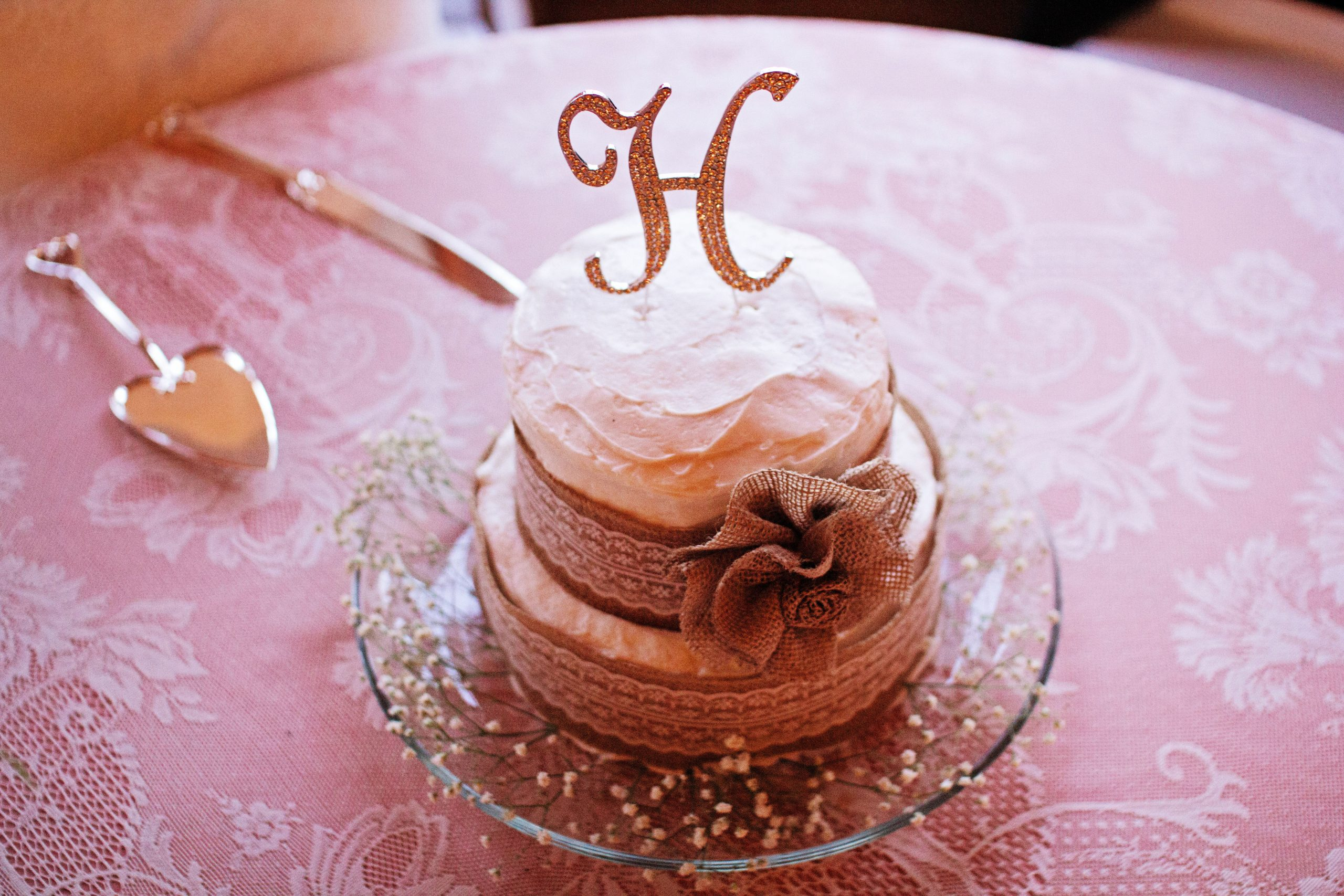 A simple two-tier wedding cake with a monogram of the first letter of the now married couple's last name photographed by Lovefusion Photography at Lakeview Farms of York, PA. Featured on Dream Weddings.
