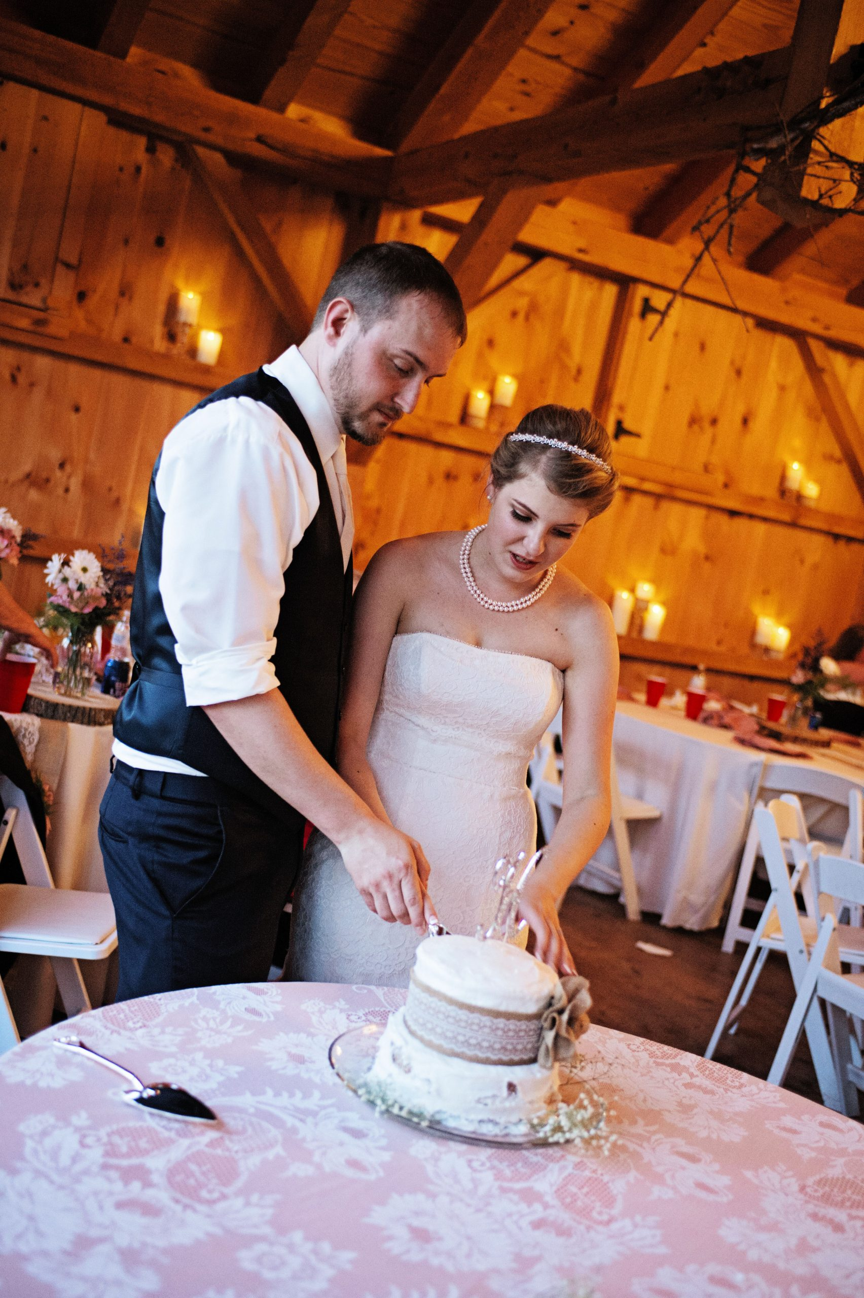 Loving couple cuts into their wedding cake at Lakeview Farms in York, PA. Lovefusion Photography had the privilege of capturing these intimate moments. Featured on Dream Weddings.