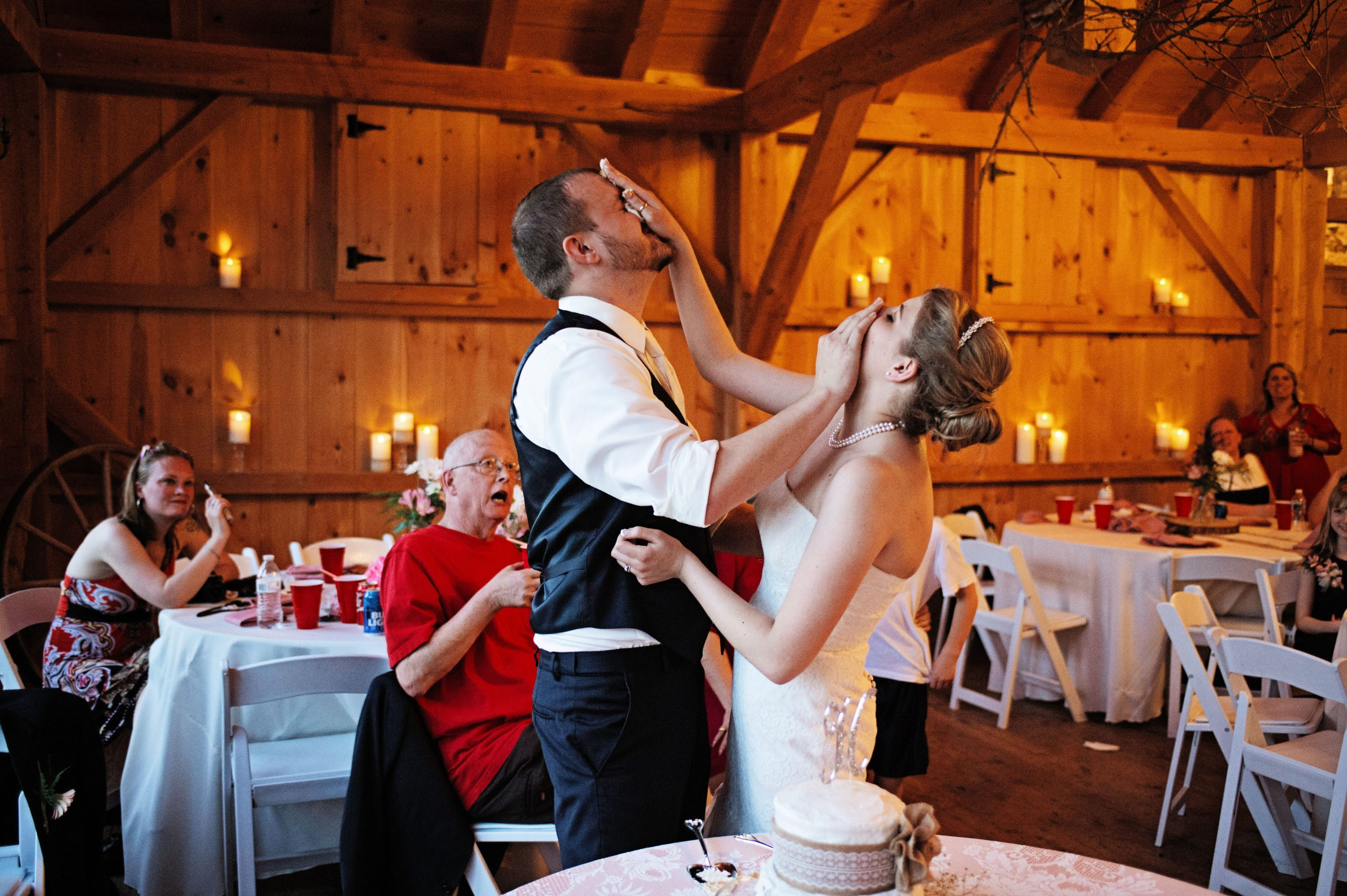 Friends and family look on in awe of the couple, Kady and Ricky, shoving cake in each others' faces at their reception at Lakeview Farms in York, PA. Captured by Lovefusion Photography, the two classically claim each other with cake. Featured on Dream Weddings.
