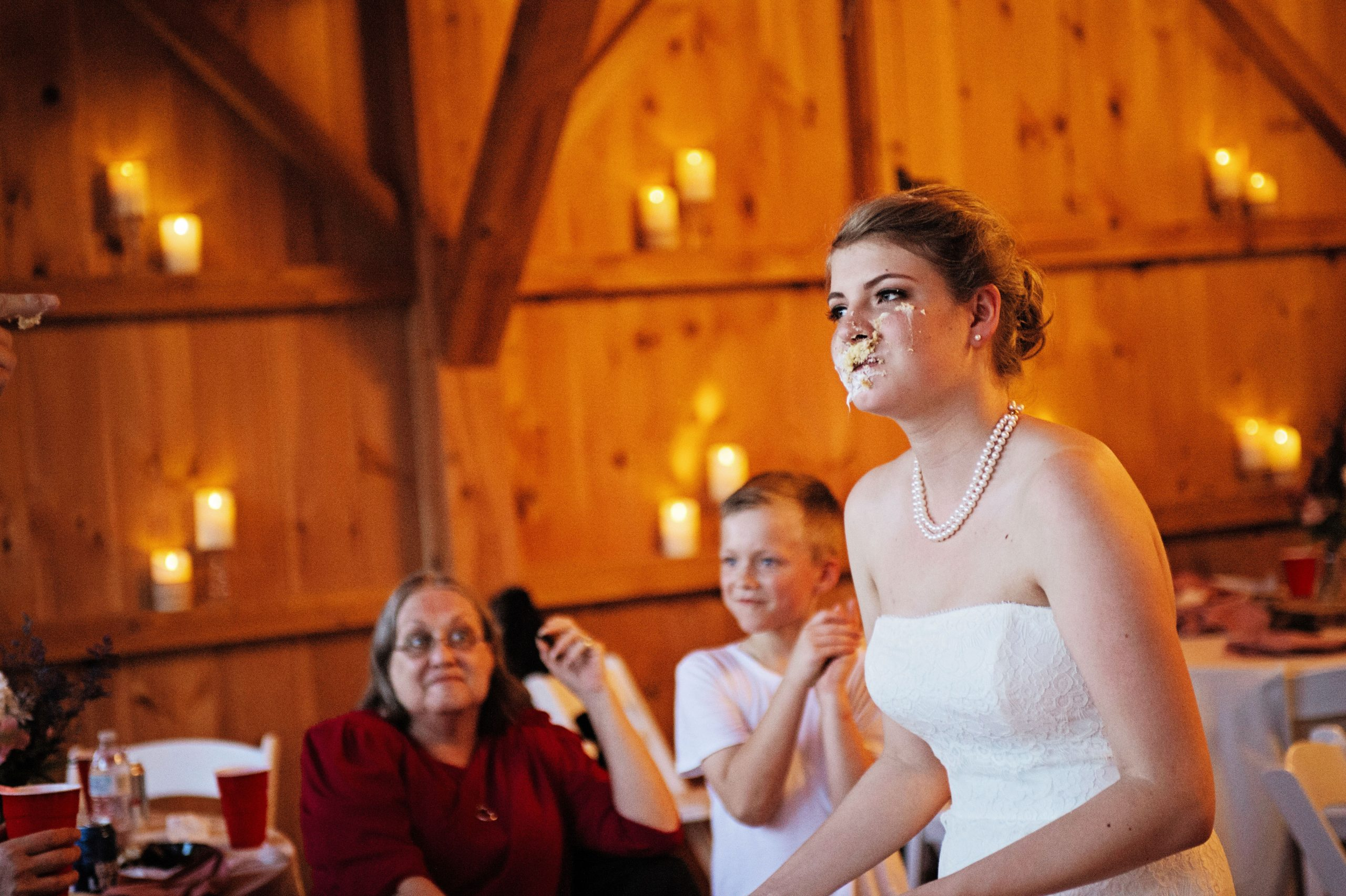 A not so pleased bride stands in the barn of Lakeview Farms in York, PA. Captured by Lovefusion photography, this rustic wedding, turned food fight is a beautiful way to celebrate your special day. Featured on Dream Weddings.
