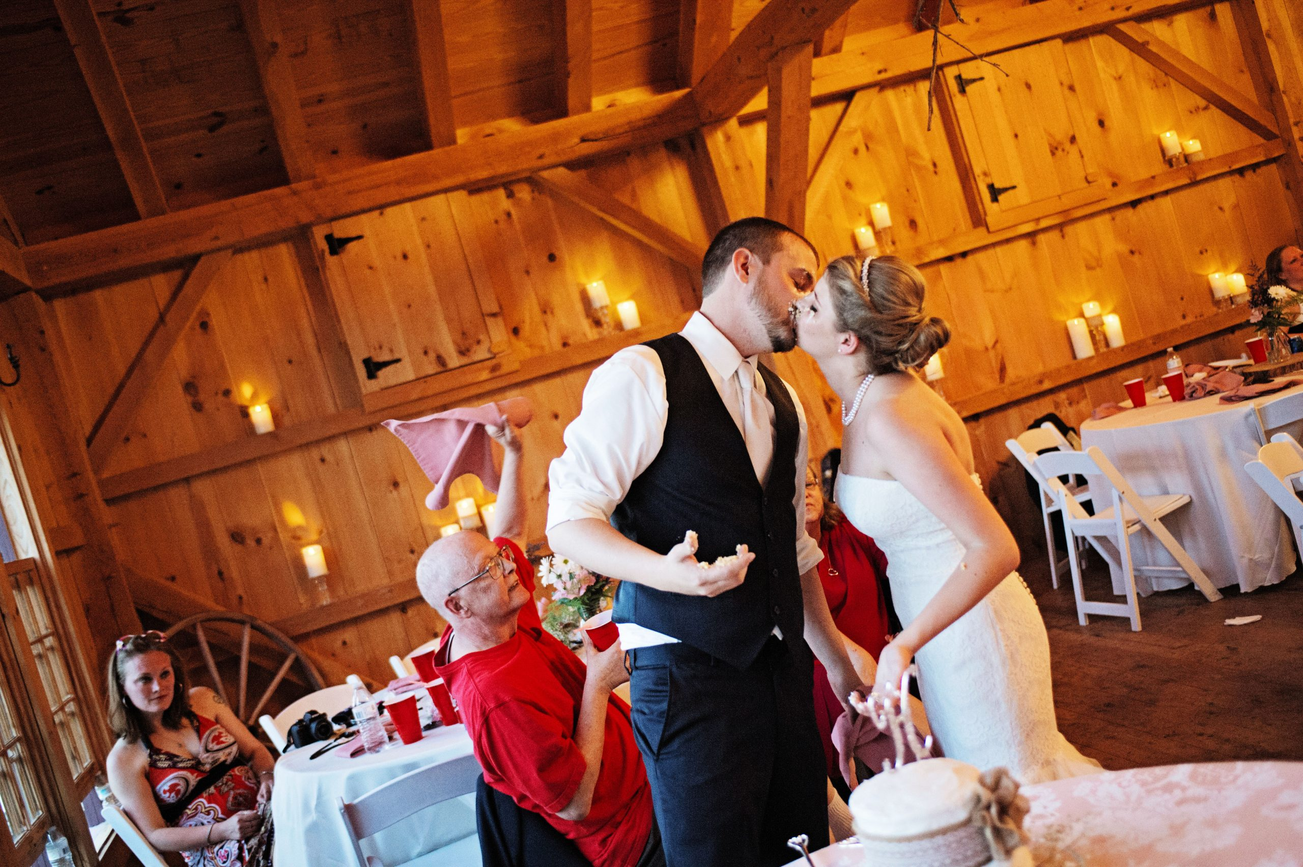 Smashed wedding cake is just as good as unsmashed wedding cake. The loving couple share a kiss at Lakeview Farms in York, PA. Photo captured by Lovefusion Photography. Featured on Dream Weddings.