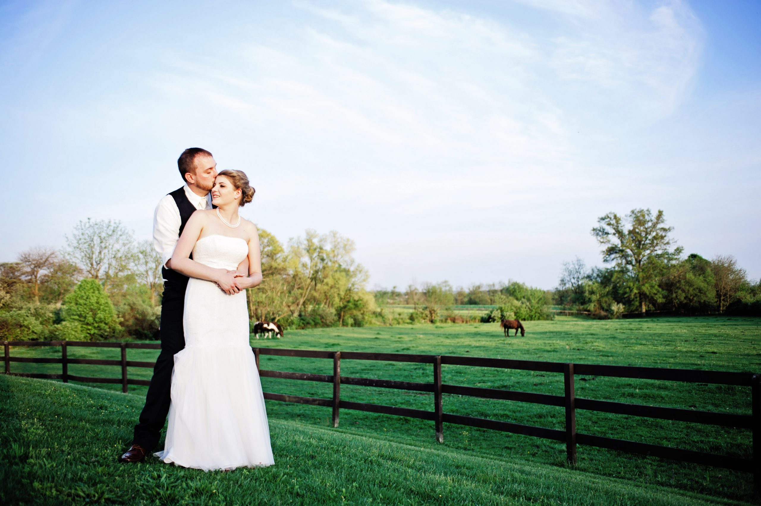 Newlyweds, Kady and Ricky warmly embrace eachother at Lakeview Farms in York, PA. Photographer, Kelsey Kinard of Lovefusion does a phenomenal job of capturing the love between the two. Featured on Dream Weddings.