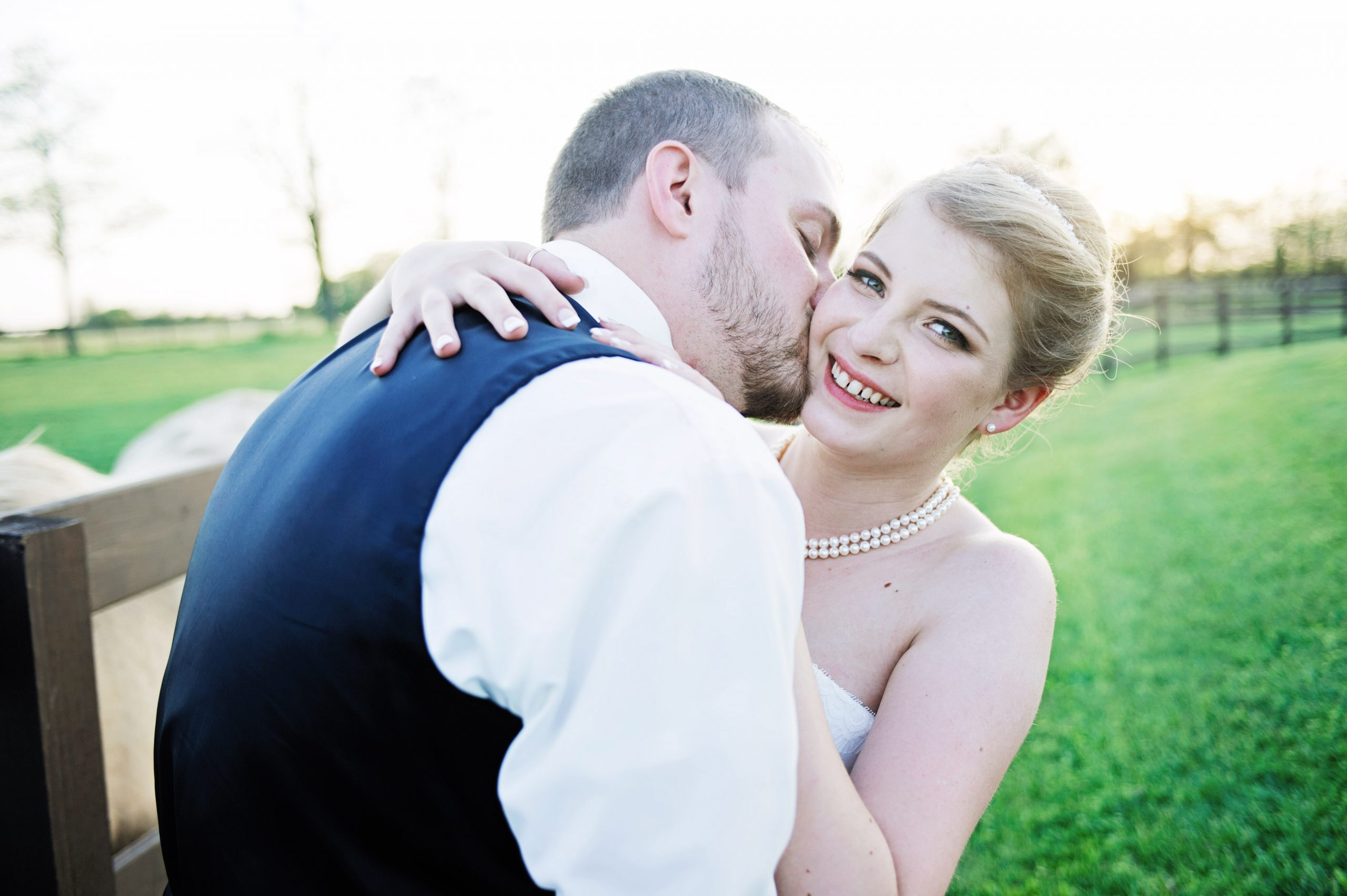 A kiss to the cheek by her hubby, Kady is smiling from ear to ear. Captured by Lovefusion Photography, Lakeview Farms of York, PA offered the perfect background. Featured on Dream Weddings.