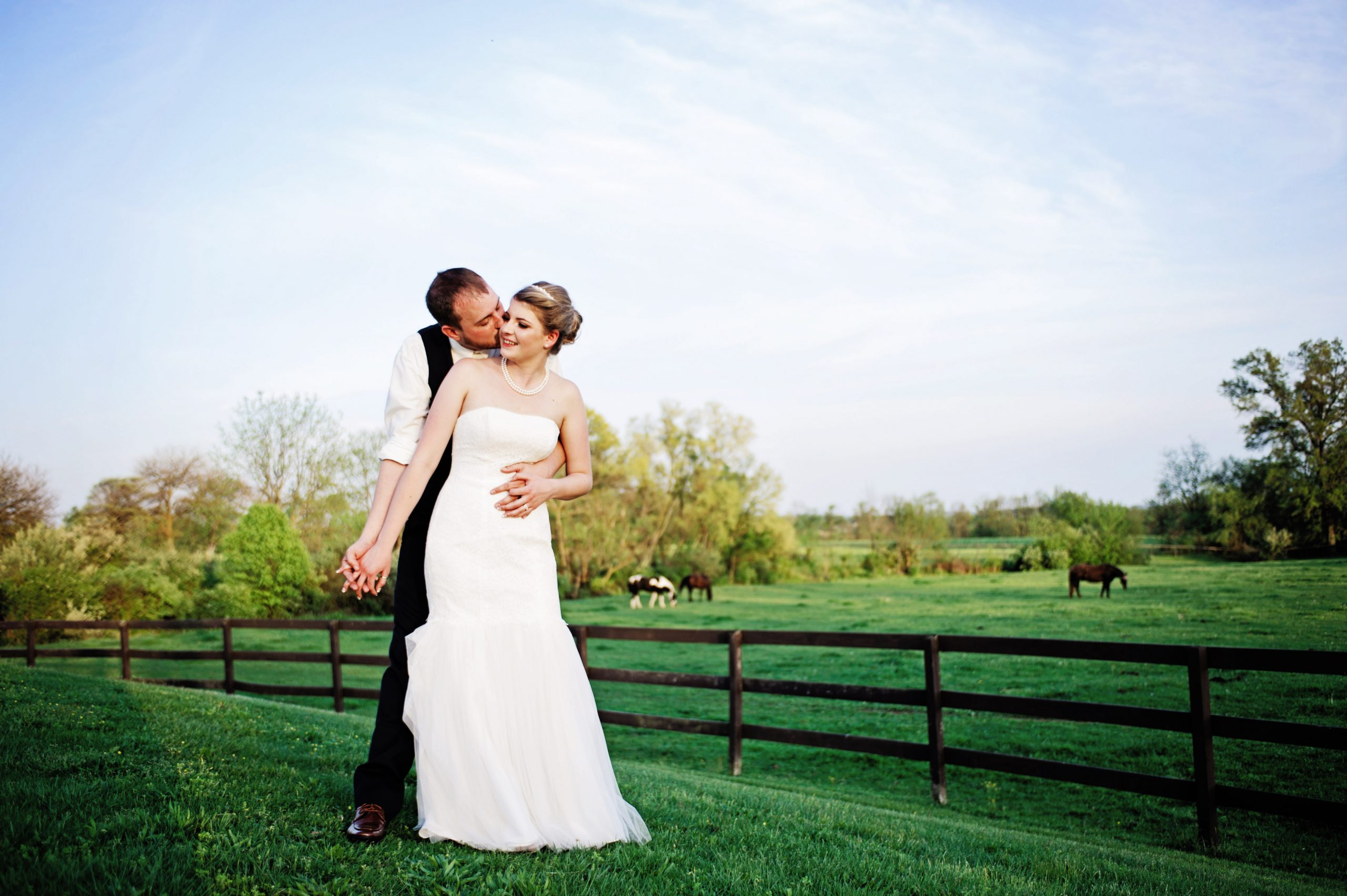 Lakeview Farms of york, PA offered a fairytale-like wedding venue for Kady and Ricky this past Spring. The two happily pose in the forefront of the property's pastures littered with horses. Featured on Dream Weddings.