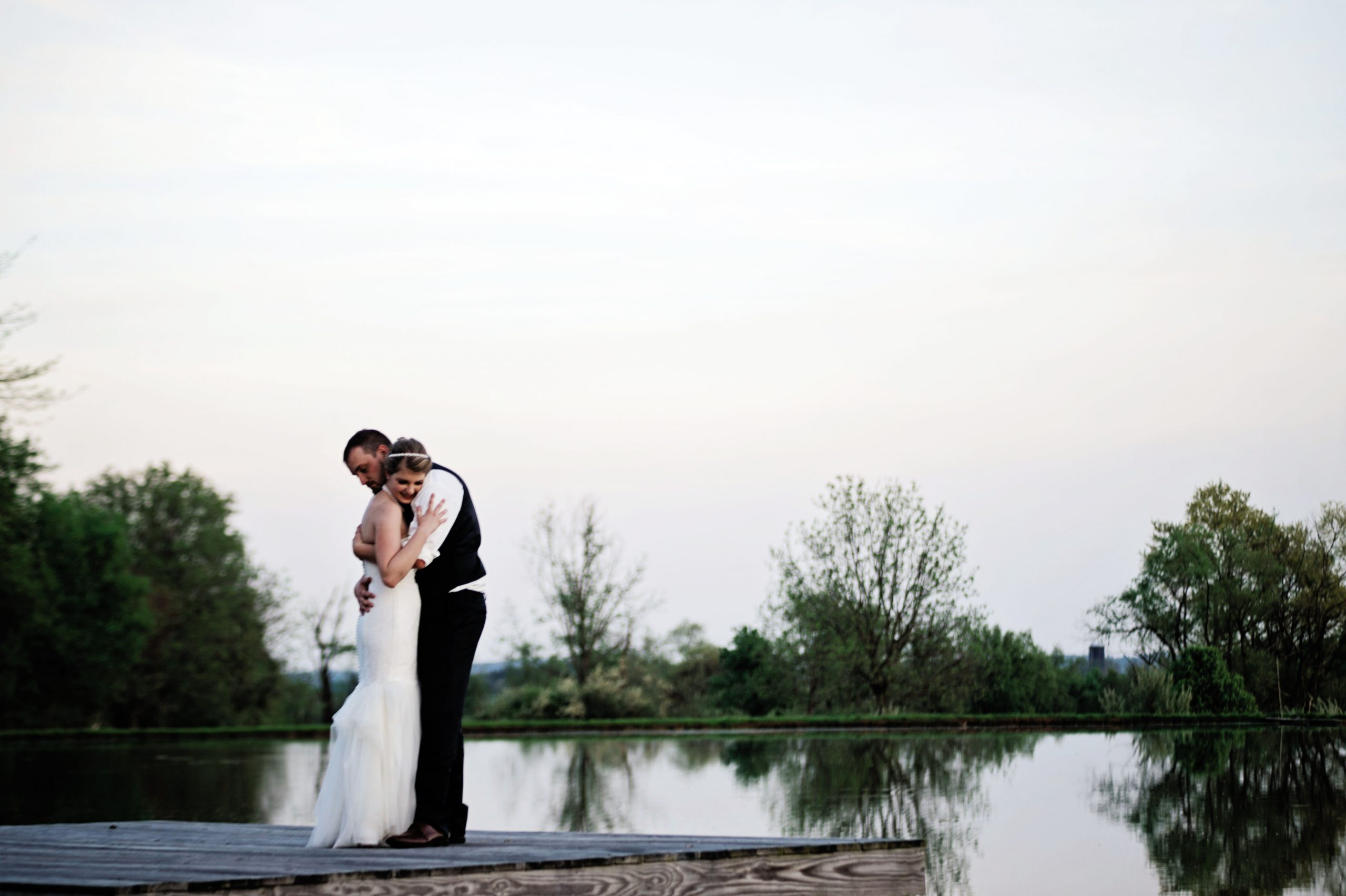 Newly wedded couple, Kady and Ricky, embrace each other on the dock at Lakeview Farms in York, PA. Lovefusion had the privilege of photographing this Spring classic romantic celebration. Featured on Dream Weddings.