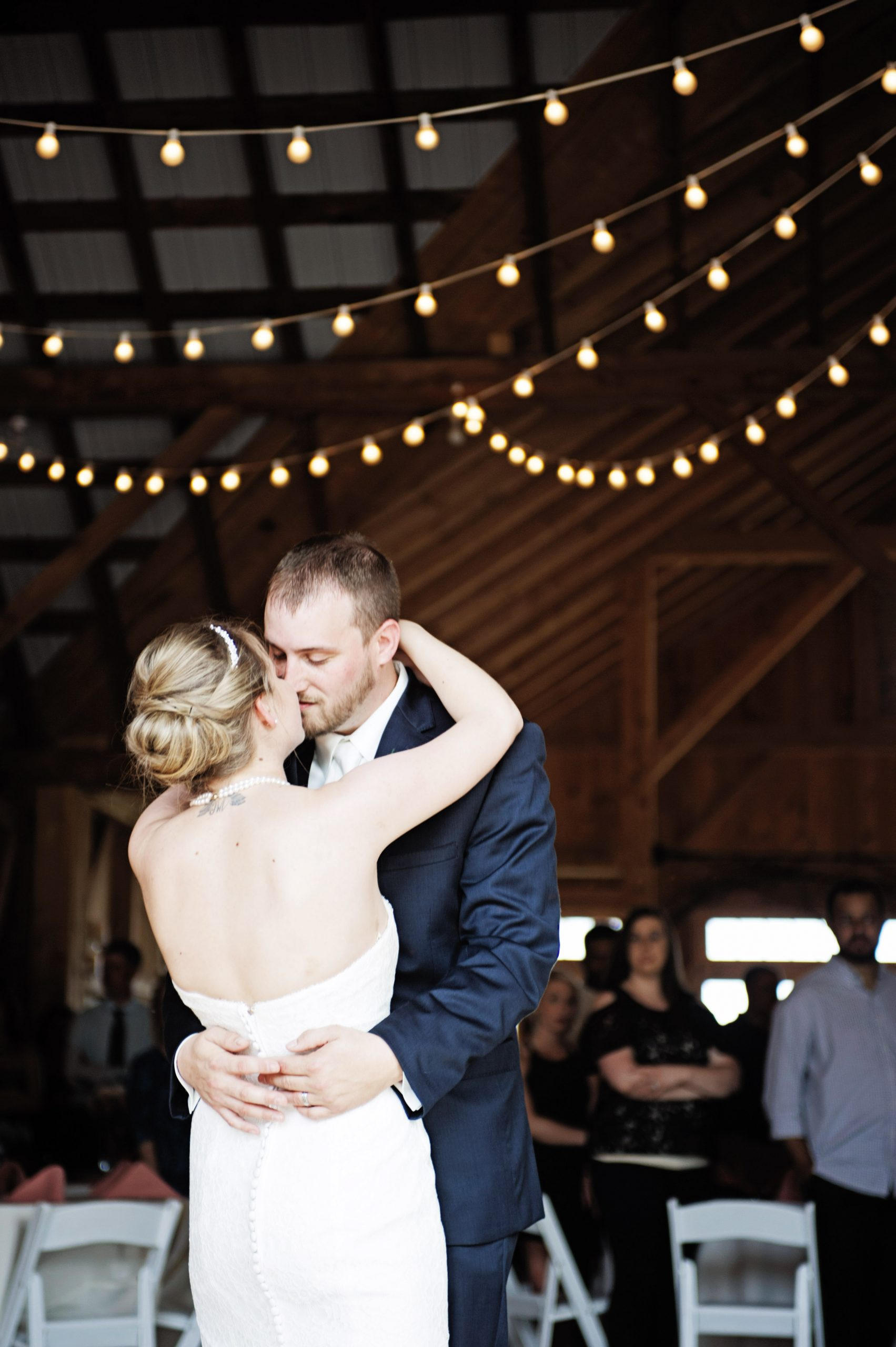 Embraced and leaning in for a kiss, this newlywed couple enjoys their splendors at Lakeview Farms of York, PA. Kelsey Kinard of Lovefusion Photography snapped a shot at just the right moment. Featured on Dream Weddings.