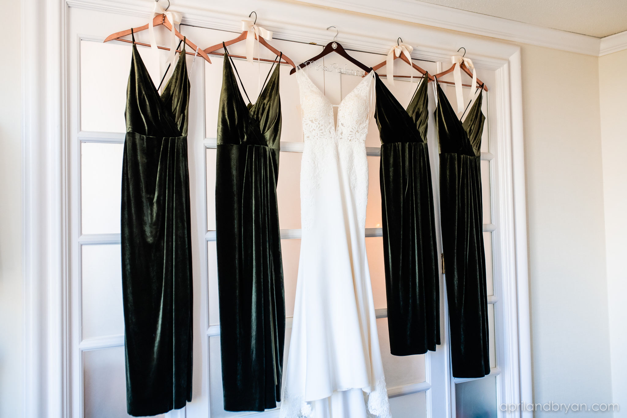 Wedding gown and bridesmaids dresses are hung in the bridal suite of the Franklin Institute in Philadelphia, PA. Shot by April & Bryan Photography. Featured on Dream Weddings.