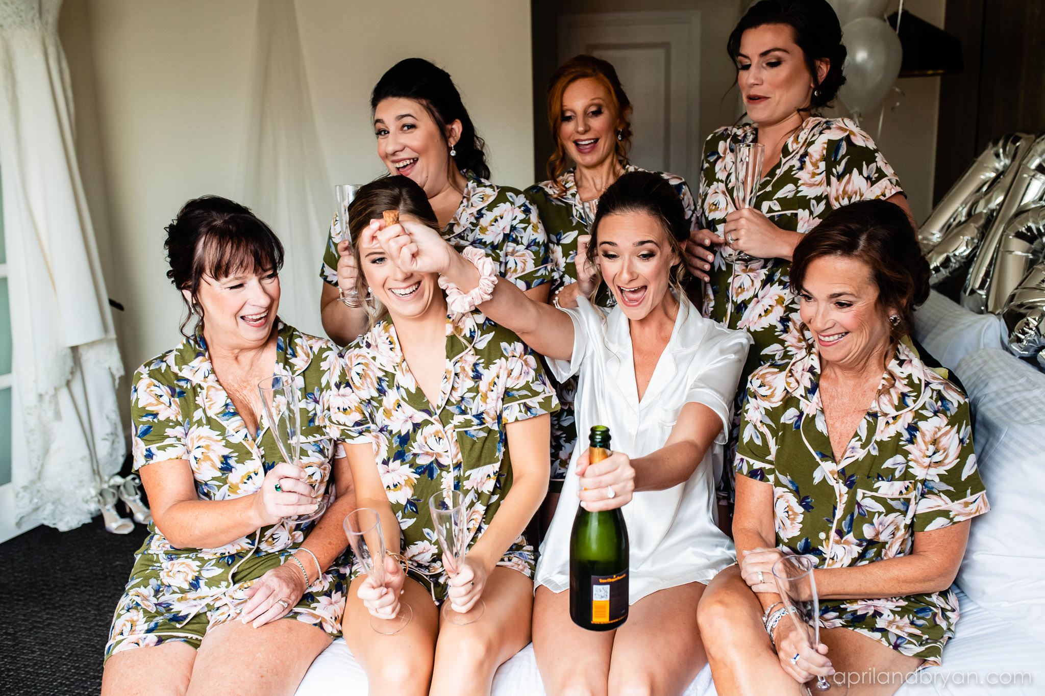 The bridal party pops champagne in the bridal suite at the Franklin Institute in Philadelphia, PA. Captured by April & Bryan Photography. Featured on Dream Weddings.