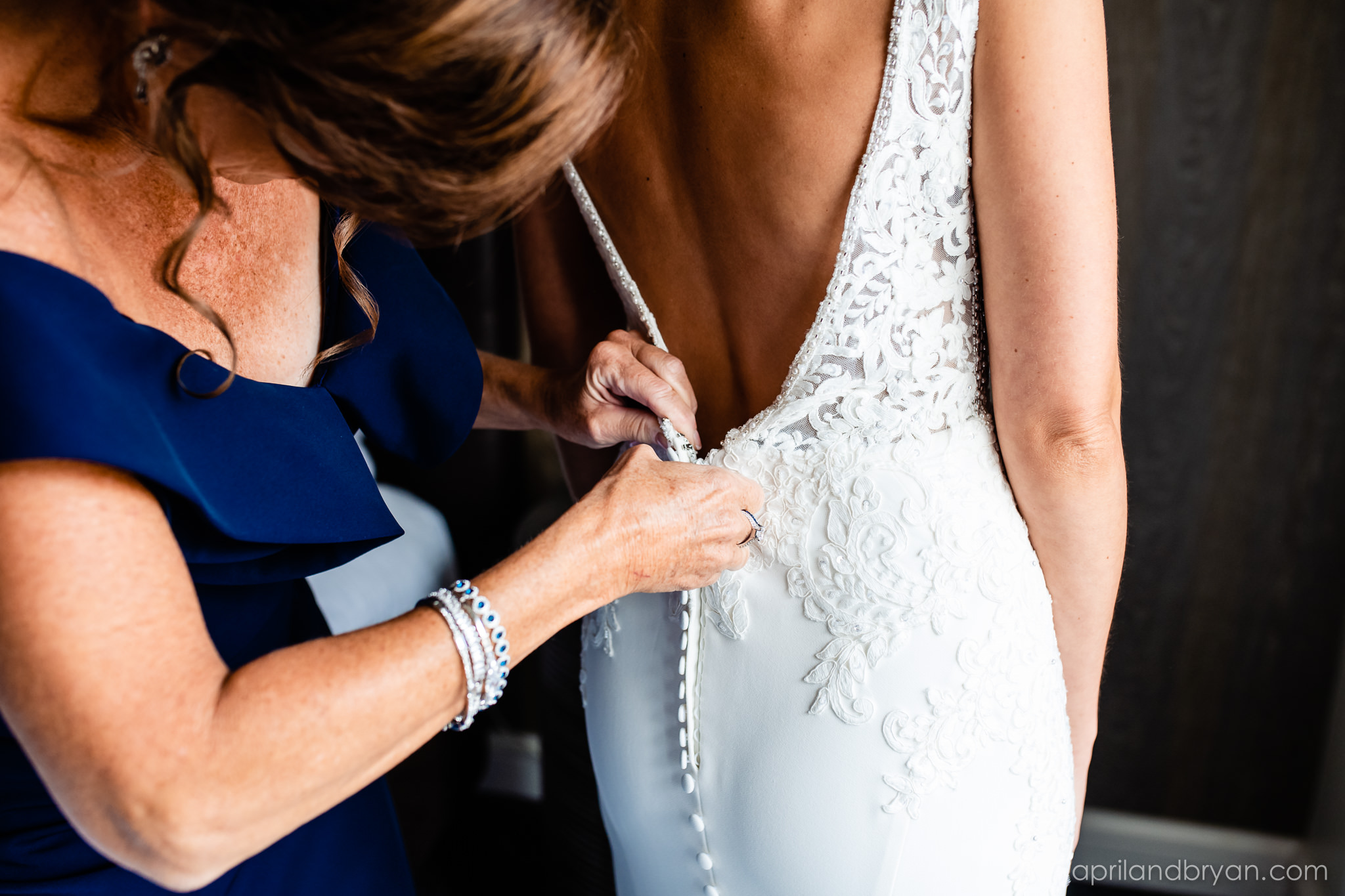 The final touches are added to the bride by her mother in the brides room at the Franklin Institute in Philadelphia. Shot by April & Bryan Photography. Featured on Dream Weddings.