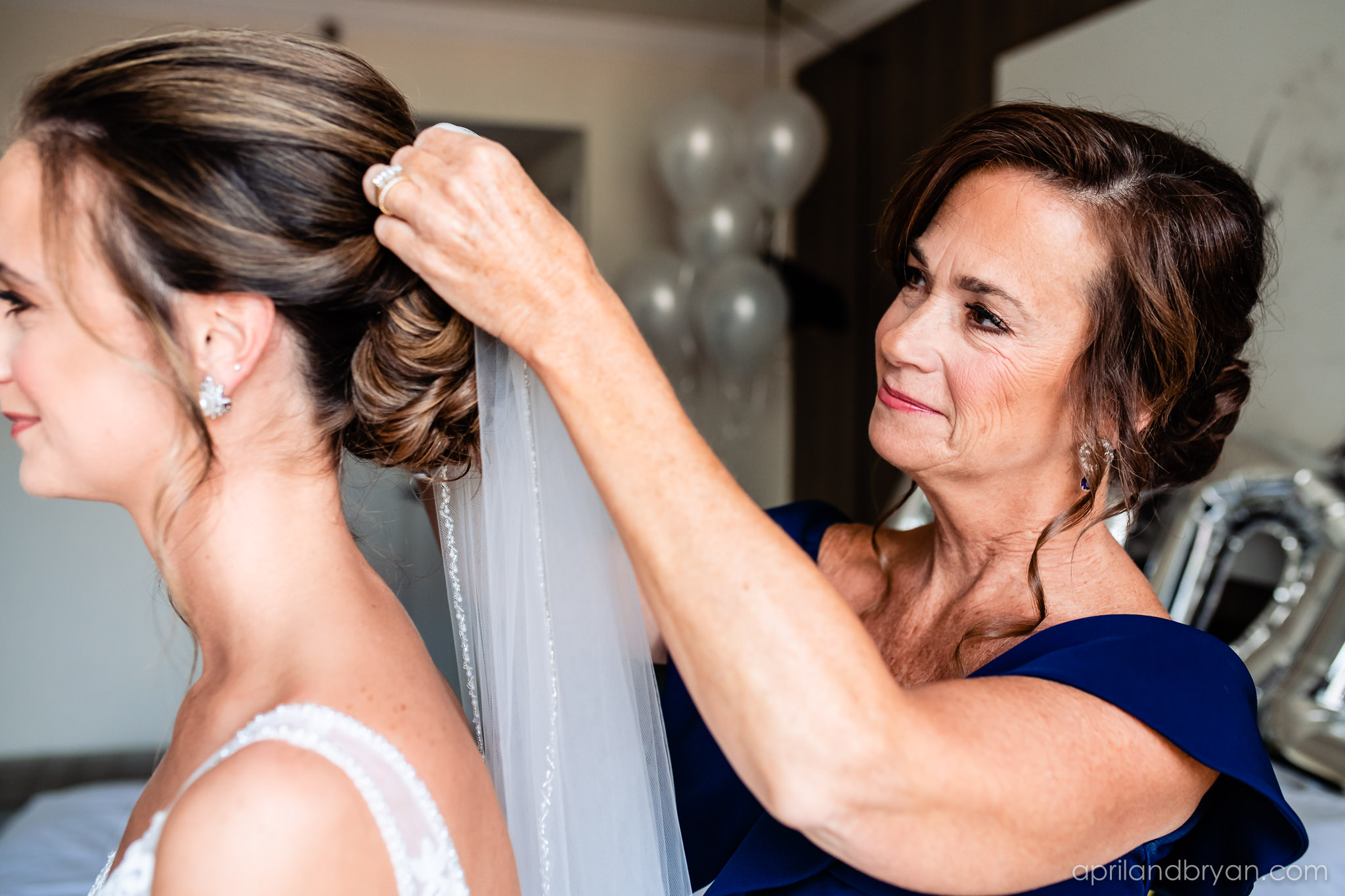 A mother helps her daughter get ready for her wedding day at the Franklin Institute in Philadelphia, PA. Moment captured by April & bryan Photography. Featured on Dream Weddings.