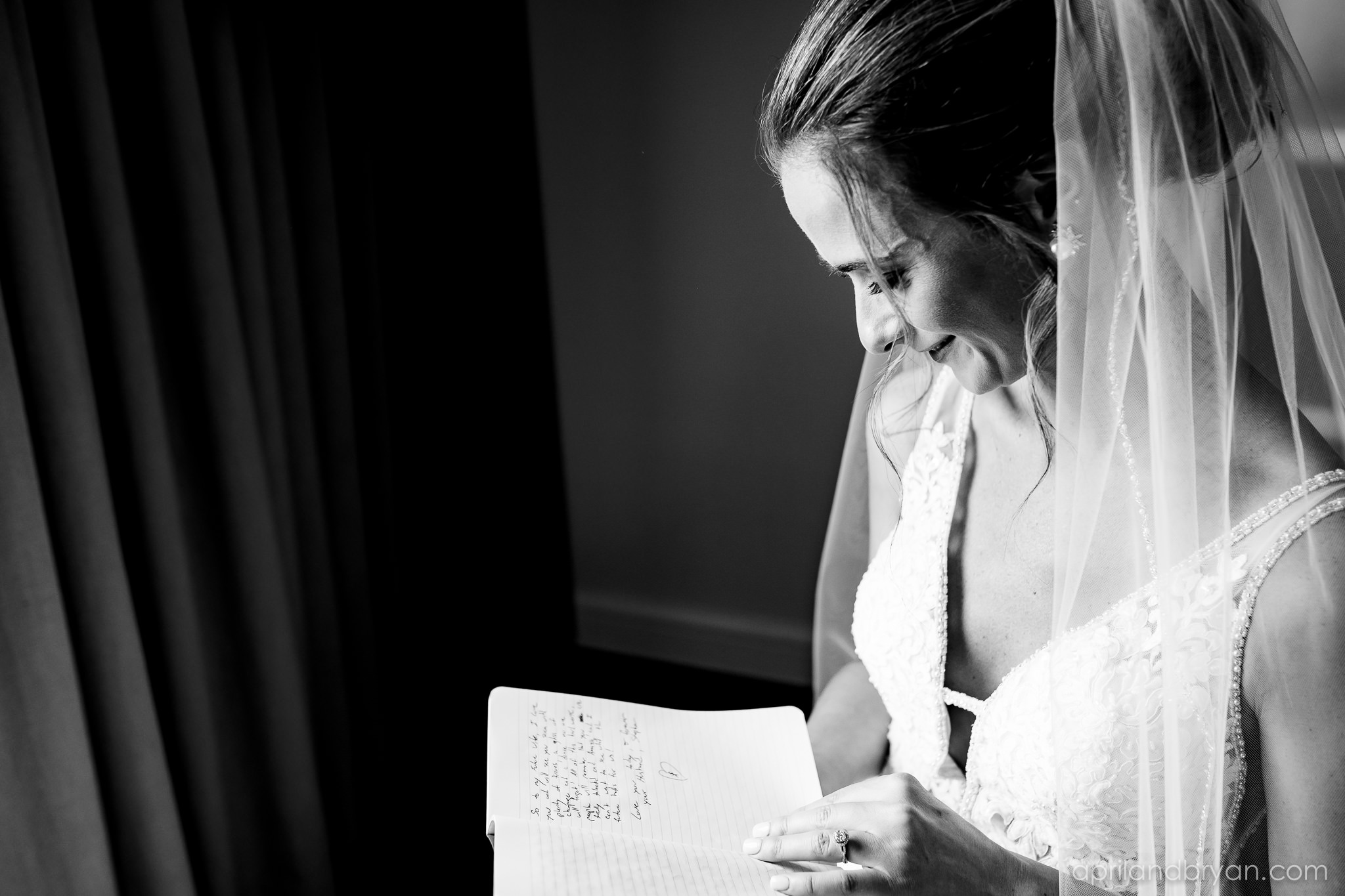 The bride reads the excerpt the groom has written for her before they wed at the Franklin Institute in Philadelphia, PA. Shot by April & Bryan Photography. Featured on Dream Weddings.