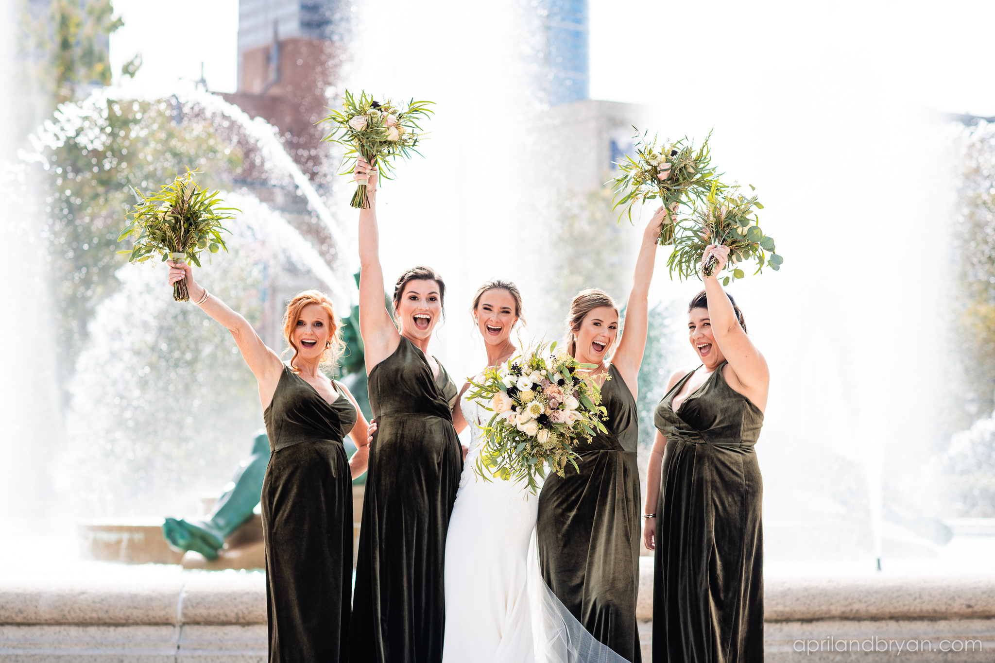 The bridal party gushes with joy in their ivy green, velvet bridesmaids dresses at the Logan Park Fountain in Philadelphia, PA. Shot by April & Bryan Photography. Featured on Dream Weddings.