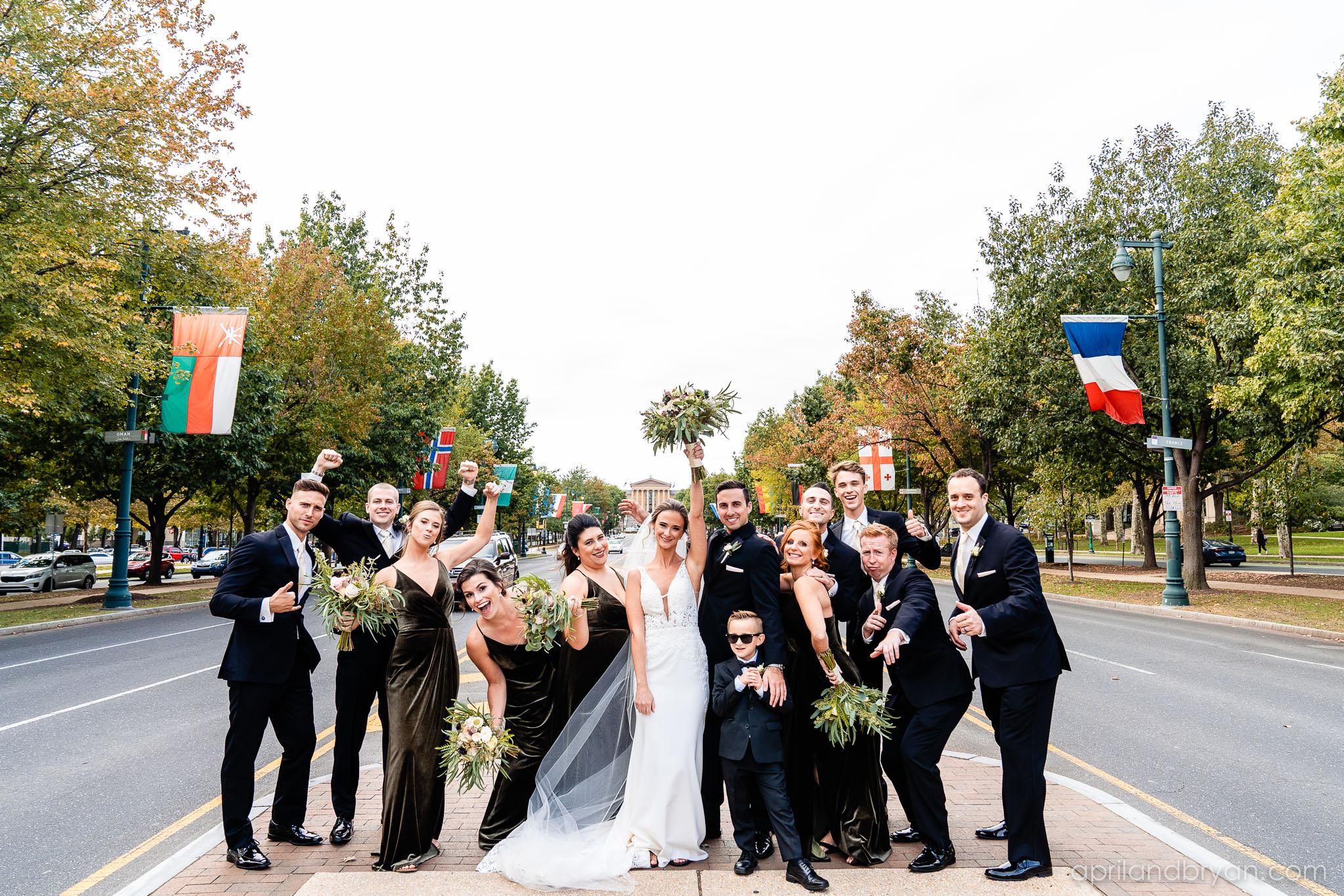 The whole bridal party poses in front of the Philadelphia Art Museum. Shot by April & Bryan Photography. Featured on Dream Weddings.