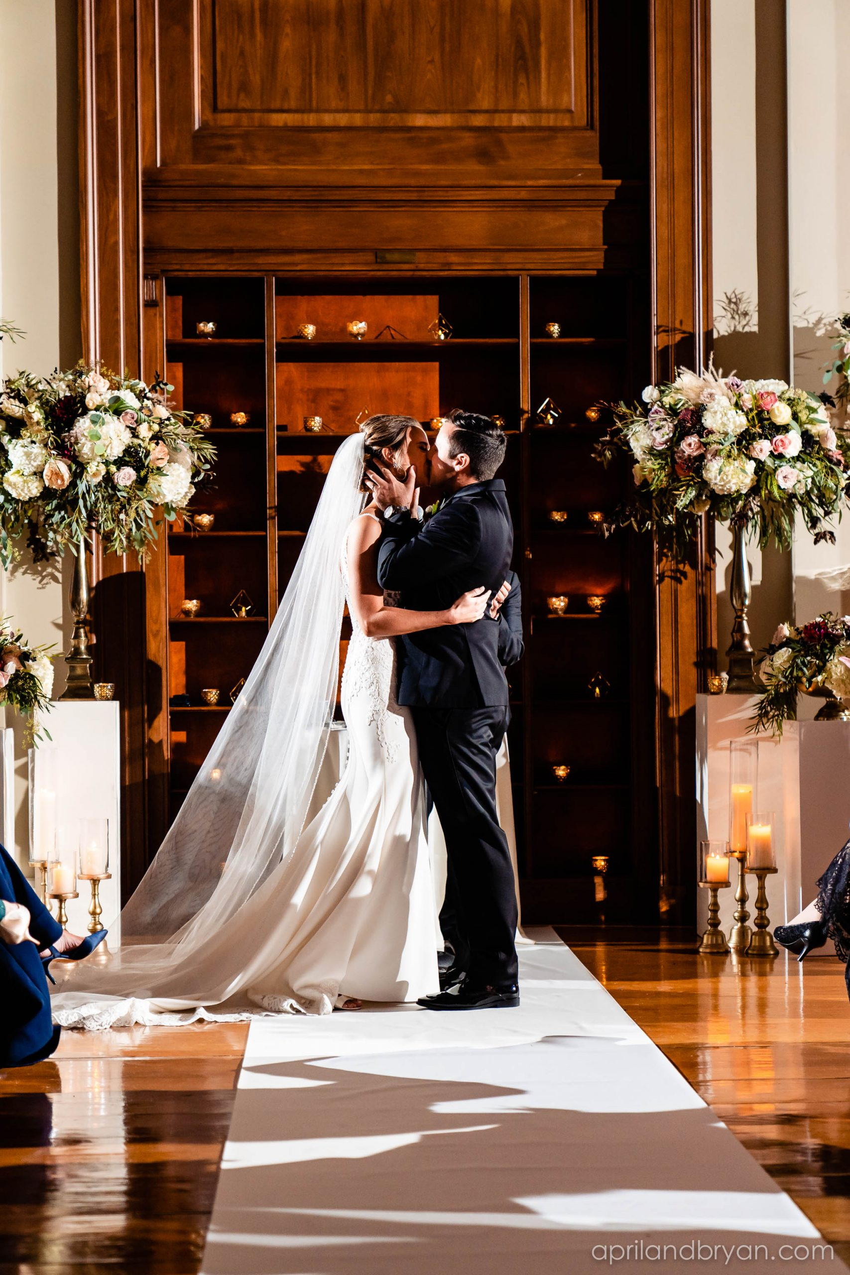 Embraced with a kiss, the couple wed and will rememeber this moment forever due to April & Bryan Photography. Featured on Dream Weddings. .